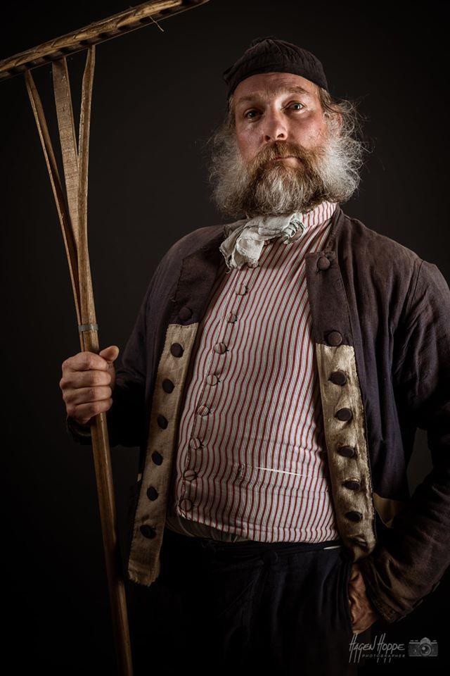 Süddeutscher Handwerker und Bauer um 1805 bis 1815 in einfacher Leinenkleidung. Die Arbeitsjacke dieser Zeit war zumeist kürzer als die Jacke im 18. Jhd. Als Knöpfe dienten Holz- oder Knochenscheiben, welche mit Stoff bezogen wurden. Hier zu sehen ist eine zweireihig geknöpfte Jacke. Sie konnte sowohl rechts als auch links überknöpft getragen werden. Die Jacke hat im Gegensatz zu Arbeitsjacken des 18. Jhd. einen Kragenansatz aber noch keinen richtigen Kragen wie nach 1815. Unter der Jacke trug man stets eine Weste, die deutlich kürzerwar als im Jahrhundert davor. Er trägt noch die klassische Culotte oder Kniebundhose, welche mit einem Latz vorne zugeknöpft wurde und einen hohen Bund besitzt. Die Strümpfe waren zumeist gestrickte Knielange Wollstrümpfe. Für Winter oder schwere Arbeit wurden auch Garmaschen darüber getragen. Als Schuhe wurden noch die üblichen Schnallenschuhe getragen. Wer kein Geld für Schnallen hatte behalf sich mit einem Riemen. Als Kopfbedeckung löste der Krempenhut den Dreispitz ab. Der Dreispitz wurde zwar noch zu besonderen Anlässen getragen und manchen Orts auch noch länger beibehalten, aber war bei weitem nicht mehr die Hauptkopfbedeckung. Je nach Arbeit wurde auch eine einfache Mütze getragen. Darsteller: Christian Vogel. Foto: Hagen Hoppe.