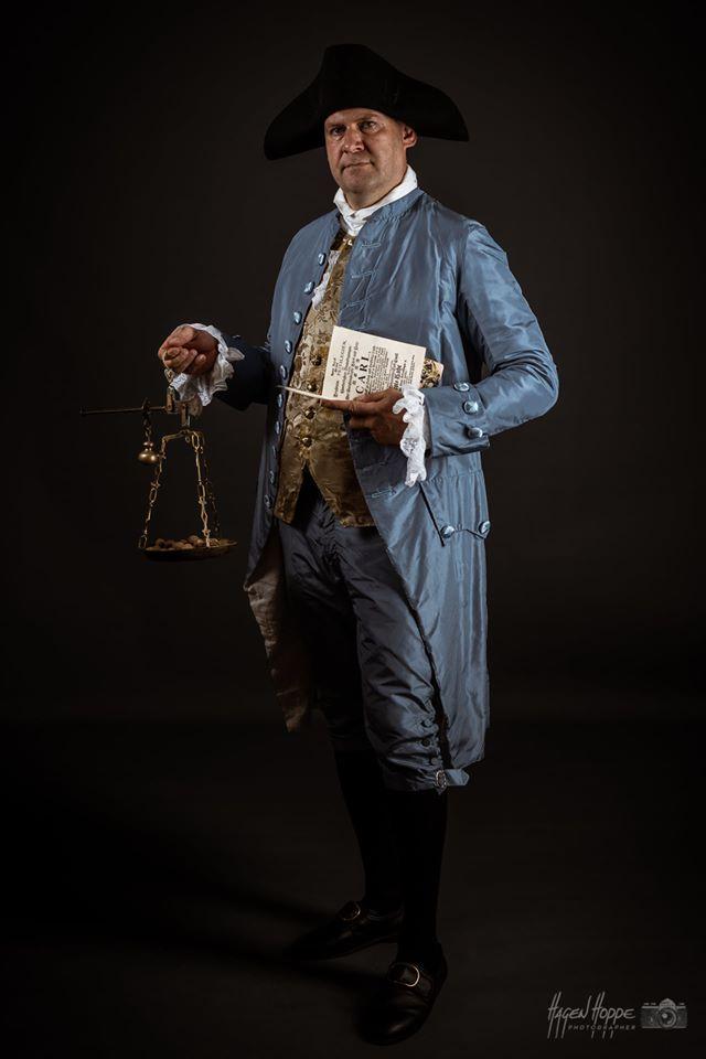 Ein reicher Kaufmann der bürgerlichen Oberschicht des 18. Jahrhunderts mit einem Just au Corps aus blauer Seide mit seidenen Posamentenknöpfen und einer Weste aus wertvollem Seidenbrokat. Dieser Anzug wurde um 1760 getragen und besteht aus drei Teilen, wie heutige Anzüge auch. Die Hose geht bis knapp über das Knie und wird mittels Metallschnallen geschlossen, diese sind aus versilbertem Messingguss. Dazu werden seidene Kniestrümpfe getragen und schwarze Lederschuhe, welche ebenfalls mit Schnallen aus Silber geschlossen werden. Ein Halstuch aus Baumwollbatist ist das Pendant zur heutigen Krawatte. Außerhalb des Hauses wird ein Hut getragen, diese Form auf dem Bild, ein Dreispitz, ist aus Wollfilz und eine sehr geläufige Form. Die Unterwäsche besteht aus einem feinen Leinenhemd mit Rüschen aus Baumwollbatist am Brustschlitz und den Ärmelmanschetten. Die Länge der Jacke und die vielen seitlichen Falten benötigen viel Stoff und zeigen zusätzlich zum hochwertigen Material durch den hohen Stoffverbrauch, wie wertvoll die Kleidung ist. Darsteller: Matthias Zimmermann. Foto: Hagen Hoppe.