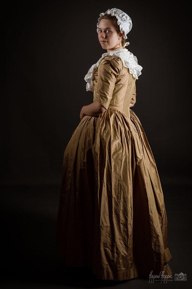 Eine Tochter der bürgerlichen Oberschicht gekleidet in eine Robe d'Anglaise aus braun gestreifter Seide. Diese besteht aus einem Überkleid mit Ärmeln, welches vorne einen Verschluss aus Haken und Ösen hat, sowie einem Unterrock aus dem gleichen Material. Zeitlich einordnen kann man dieses Kleid in die 1770er Jahre. Besonders verbreitet war es, wie der Name schon sagt im englischsprachigen Raum, allerdings fand man diese Mode auch im Europa des 18. Jahrhunderts. Als Accessoires tropfenförmige Salzwasserperlenohrringe und ein Collier aus runden Salzwasserperlen, welches mit einem Seidenband geschlossen wird. Die Unterwäsche besteht aus einem feinen Leinenunterhemd, Seidenstrümpfen und einer Schnürbrust (Korsett), welches mit Fischbeinersatz verstärkt ist, mit Leinen und Seide bezogen und mit Wildleder eingefasst. Darstellerin Jara Uphoff. Foto: Hagen Hoppe.
