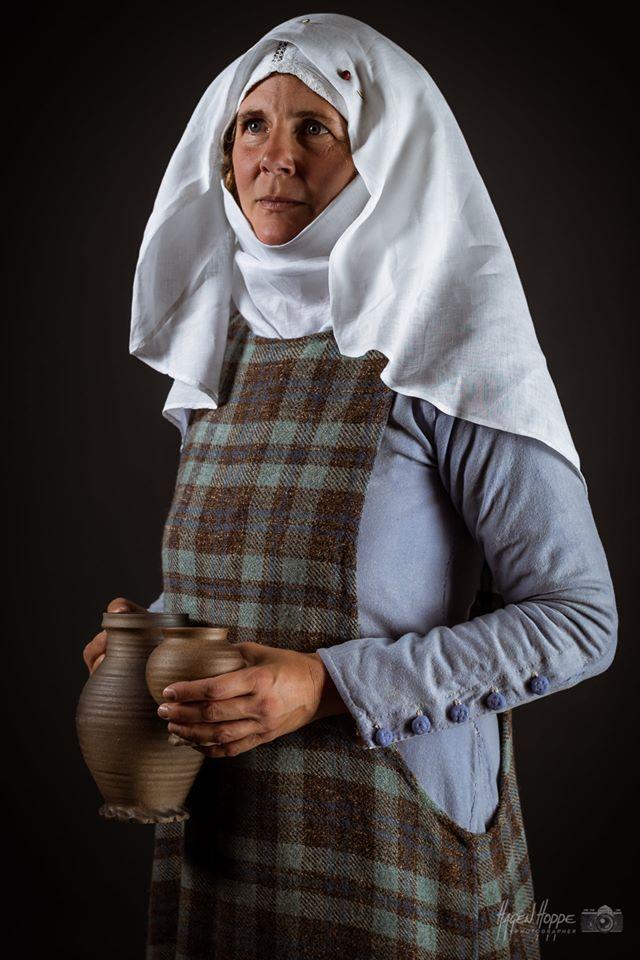 Handwerkergattin in Alltagskleidung aus Frankfurt um 1340. Über einem gebleichten leinernen Unterkleid, genähten Wollstrümpfen und wendegenähten Schuhen trägt sie ein blass-waidblaues Wollkleid mit Stoffknöpfen am Halsausschnitt und an den Ärmeln und darüber ein sog. Höllenfensterkleid mit gewebtem Karomuster.  Auf dem Kopf trägt sie eine enganliegende Haube, die mittels um den Kopf geschlungenen Bändern befestigt ist. An dieser ist ein Schleier mit Schmuckadeln befestigt. Der Hals wird von einem Wimpel bedeckt. Accessoires wie der Gürtel und daran hängende Gebrauchsgegenstände werden auf dem Kleid, also unter dem Überkleid getragen. In der Hand trägt sie einfache Gebrauchskeramik, sog. Siegburger Ware, die auch in Frankfurt gehandelt wurde. Darstellerin: Caroline v. Bernuth. Foto: Hagen Hoppe.