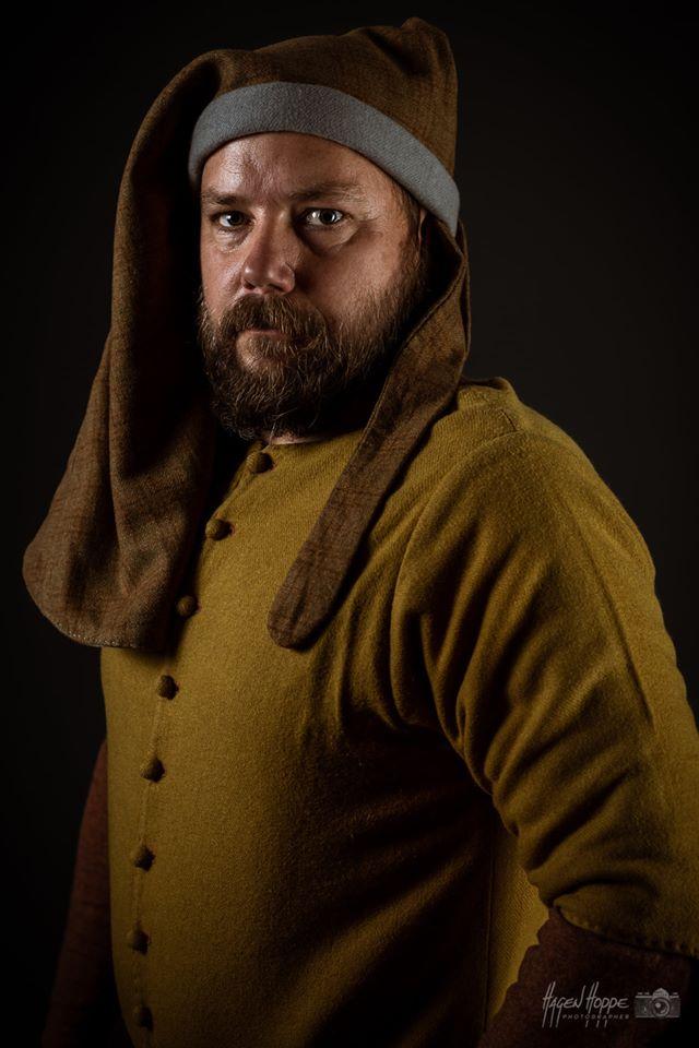 Handwerker in Sonntagskleidung aus Frankfurt um 1340.  Über der gebleichten, leinenen Unterbekleidung, bestehend aus Hemd und Bruche, sowie Indigo gefärbten Hosen, die an der Bruche befestigt sind, trägt er einen rostroten, am Ausschnitt und an den Ärmeln geknöpften Wollkittel. Darüber trägt er einen birkenblattgefärbten, grünen Wollkittel mit Löffelärmeln. Der Löffelärmelkittel ist mit krappgefärbter Wolle gefüttert. Diese Art der Ärmel waren eine zeitlich sehr begrenzte Modeerscheinung. Der Träger suggerierte mit solch unpraktischen modischen Details, dass er nicht körperlich arbeiten musste. Zu diesen Details gehören auch die wendegenähten Schlupfschuhe, sowie die zum Gugelhut aufgerollte Gugel auf dem Kopf. Der mit Zinnbeschlägen verzierte Gürtel, der daran hängende Hodendolch, sowie der kunstvoll mit Seide bestickte Almosenbeutel vervollständigen das Bild eines selbstbewussten Bürgers im Sonntagsstaat.  Darsteller: Constantin v. Bernuth. Foto: Hagen Hoppe.