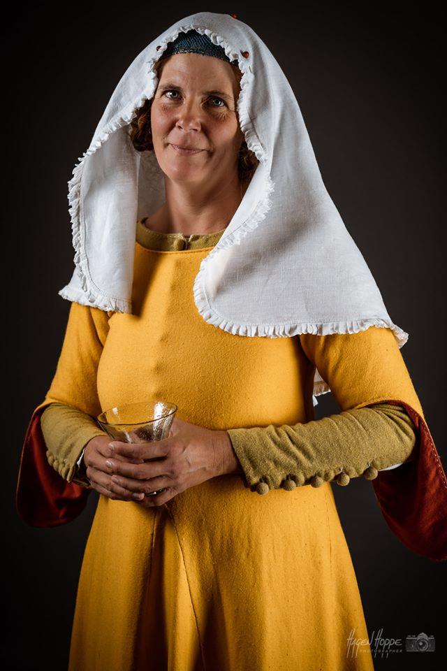 Handwerkergattin in Sonntagskleidung aus Frankfurt um 1340. Über einem leinernen Unterkleid, genähten Wollstrümpfen und wendegenähten Schuhen trägt sie ein birkenblattgefärbtes grünes Wollkleid (Cotte) mit Stoffknöpfen am Halsausschnitt und an den Ärmeln.Die ab etwa 1300 vermehrt verwendeten Knöpfe ermöglichen es, die Kleidung im Vergleich zu hochmittelalterlicher Mode figurbetonter zu schneidern. Darüber trägt sie ein sog. Löffelärmelkleid (Sucknei) aus gelber Wolle mit krappgefärbtem Ärmelfutter. Diese Art der Ärmel waren eine zeitlich sehr begrenzte Modeerscheinung. Der Träger suggerierte mit solch unpraktischen modischen Details u.a., dass er nicht körperlich arbeiten musste. Auf dem Kopf trägt sie ein seidenes Haarnetz, über einer zeittypischen Frisur. Über dem Haarnetz trägt sie einen mit Schmucknadeln festgesteckten, sehr modischen Schleier aus feinem Leinen mit angenähter gekräuselter Kante, einen sog. Kruseler.  In der Hand trägt sie ein für die Zeit typisches grünes Glas.  Darstellerin: Caroline v. Bernuth. Foto: Hagen Hoppe.