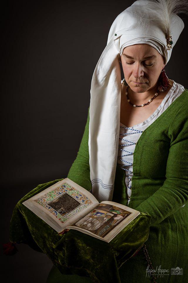 Wohlhabende Frankfurter Dame um 1475. Das Kleid, aus einem auffällig grün gefärbten, feinen Wollstoff ist sehr modern und gewagt geschnitten. Am Oberkörper eng anliegend, zeigt es viel vom darunter getragenen Hemdkleid, was wenige Jahrzehnte zuvor undenkbar gewesen wäre.  Den Stand stellt die Trägerin aber mit einer Vielzahl an Accessoires heraus:  An der Haube aus einem feinen Leinenstoff mit eingewebten Streifen ist eine vergoldete Agraffe mit einem Reiherstutz befestigt. Dieser ist im 15, Jahrhundert ausgesprochen populär und besteht aus etwa 100 einzelnen Reiherfedern. Auch Halskette, Gürtel und der Paternoster zeigen deutlich den Stand der Patrizierin. Auch wenn Frauen im Spätmittelalter keineswegs gleichberechtigt waren, finden sich doch etliche Beispiele für Frauen die eigene Gewerbe betrieben, Wohlstand ansammelten und sogar Mitspracherechte in der Selbstverwaltung der Städte erlangten. Darstellerin: Andrea Perkuhn. Foto: Hagen Hoppe.