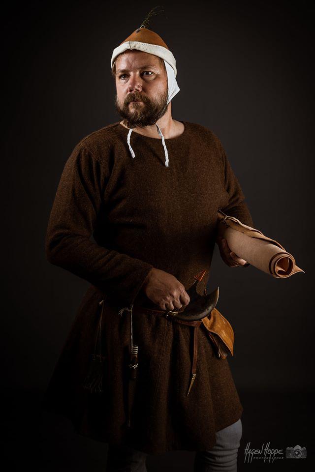 Handwerker in Alltagskleidung aus Frankfurt um 1340. Über der gebleichten, leinenen Unterbekleidung, bestehend aus Hemd und Bruche, sowie blassblau gefärbten Hosen, die an der Bruche befestigt sind, trägt er einen schlichten, naturbraunen Arbeitskittel.  Dazu trägt er wendegenähte sog. Knöpfriegel Lederschuhe. Auf dem Kopf trägt er über einer leinenen Bundhaube einen für die Zeit typischen stoffgefütterten Filzhut. An einem schlichten Gürtel mit Buntmetallschließe hängen ein Geldbeutel, ein Gebrauchsmesser in einer Messerscheide und eine Gürteltasche für die Dinge des täglichen Bedarfs. In seiner Hand hält er einen für Lederhandwerker typischen Schusterhalbmond und ein Vorrat an Kalbsleder unter dem Arm. Darsteller: Constantin v. Bernuth. Foto: Hagen Hoppe.