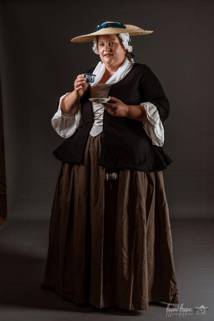 Bürgerliche Frau Mitte 18. Jahrhundert. Orientiert an zeitgenössischen Gemälden von beispielsweise Johann Christian Fiedler und Justus Juncker. Die Haube ist aus feinem, weißen Leinen gefertigt. Der Gesichtsausschnitt ist gerafft und mit einer einfach gehaltenen Spitze eingefasst. Die blaue Jacke ist aus dunkler Wolle genäht und mit einem Leinenstoff gefüttert. An den Ärmelenden befinden sich die Engageants. Engageants sind angesetzte, oft auch nur angeheftete oder angesteckte Ärmelattrappen, in diesem Fall aus feiner, sehr dünner Wolle. Diese werden je nach Anlass getragen und bilden hier einen feineren Ärmelabschluss. In höheren Kreisen auch aus edleren Materialien und zusätzlich mehrlagigen Spitzenbesatz. Diese bilden für das 18. Jahrhundert ein klassisches Kleidungsdetail. Im Gegensatz dazu findet man an der gestreiften aus Leinen gefertigten Jacke lediglich ein gekrempeltes Ärmelende vor. In der Front sind hier beide Jacken mit einem Stecker und einer darüber liegenden Schnürung geschlossen. Die Stecker zeichnen hier das klassische Bild und werden oft irrtümlich als offen getragene Schnürbrust (umgangssprachlich: Korsett) gedeutet. Um die nötige Saumweite zu erreichen, sind die Röcke an der Bundkante in mehrere Falten gelegt. Beide Röcke sind hier aus Leinenstoff. Beidseitig haben sie eine überlappende, in den Falten nicht sichtbare Öffnung, um in die darunterliegenden Poschen (Taschen) greifen zu können. Die schwarze Leinenschürze hat hier eine für das 18. Jahrhundert sehr klassische hochgezogene Front. Schürzen wurden nicht nur beim Erledigen von hauswirtschaftlichen Tätigkeiten getragen, sondern wie viele Gemälde zeigen (bspw. Philippe Mercier oder oben genannte), auch bei Handarbeiten oder in höheren Ständen als Kleidungsaccessoire aus feineren Stoffen (bspw. Seide) genutzt.  Darstellerin: Sahra Hirschfeld. Foto: Hagen Hoppe.