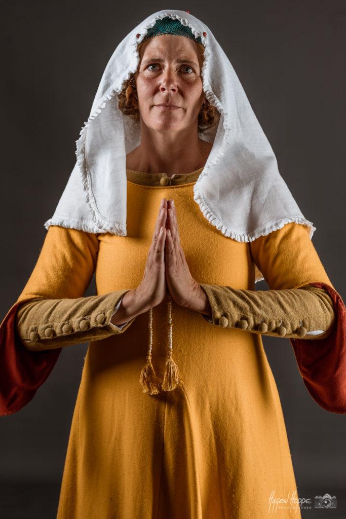 Handwerkergattin in Sonntagskleidung aus Frankfurt um 1340. Über einem leinernen Unterkleid, genähten Wollstrümpfen und wendegenähten Schuhen trägt sie ein birkenblattgefärbtes grünes Wollkleid (Cotte) mit Stoffknöpfen am Halsausschnitt und an den Ärmeln.Die ab etwa 1300 vermehrt verwendeten Knöpfe ermöglichen es, die Kleidung im Vergleich zu hochmittelalterlicher Mode figurbetonter zu schneidern. Darüber trägt sie ein sog. Löffelärmelkleid (Sucknei) aus gelber Wolle mit krappgefärbtem Ärmelfutter. Diese Art der Ärmel waren eine zeitlich sehr begrenzte Modeerscheinung. Der Träger suggerierte mit solch unpraktischen modischen Details u.a., dass er nicht körperlich arbeiten musste. Auf dem Kopf trägt sie ein seidenes Haarnetz, über einer zeittypischen Frisur. Über dem Haarnetz trägt sie einen mit Schmucknadeln festgesteckten, sehr modischen Schleier aus feinem Leinen mit angenähter gekräuselter Kante, einen sog. Kruseler. Darstellerin: Caroline v. Bernuth. Foto: Hagen Hoppe.